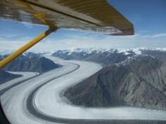 The Yukon - There are no roads in Kluane National Park, no easy way to see the glaciers and peaks reaching nearly 20,000 feet…except by taking to the air. A banked left turn took us up the Kashkawulsh River valley to the great Kashkawulsh glacier with its precisely defined dark moraines striped against the white glacier ice. Into the heart of the St Elias Range, Mount Logan the highest peak of all is mantled with wisps of cloud in the distance...