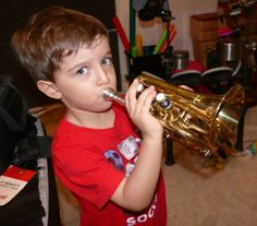 Jonah essaye la trompette de poche au Tout Petit Conservatoire.