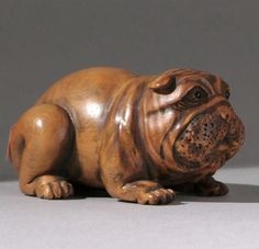 WOOD NETSUKE 19th Century By Gyokumatsu. In the form of a reclining dog with comic expression and inlaid eyes.