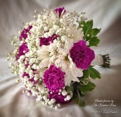 Hand tied brides bouquet of purple carnations and white daisies, accented with babies breath. Wrapped with double faced white satin ribbon