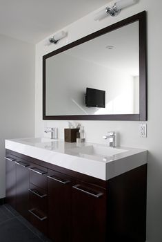 Modern bathroom design with gray slate tiles floor, espresso stained double bathroom vanity with white quartz countertop, modern hardware & faucets, espresso stained framed bathroom mirror and double sconces.