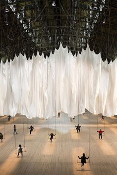 "~""Massive"" Interactive Indoor swing by Ann Hamilton, at the Park Avenue Armory... invites an interactive audience to revisit their playful childhood and ride the 42 swings that have been set up. The 55,000-square-foot space boasts a giant billowing white curtain that separates the hall..."
