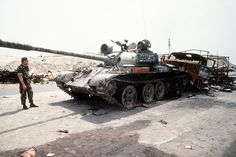 A destroyed Iraqi T-55 and supply truck, painted with graffiti by Coalition troops, along the highway between Kuwait City and Basra, Iraq, following the retreat of Iraqi forces from Kuwait during Operation Desert Storm.