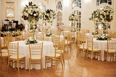 ballroom is dressed in white and gold for the wedding reception. tall lush arrangements on gold pedestals of white garden roses, white hydrangea, white spray roses, white tulips, white ranunculus, white larkspur, white veronica, button chamomile, magnolia greens, eucalyptus greenery and vines.  trios of brass candlesticks with pale grey taper candles complete the tables.