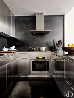 The kitchen in a Manhattan duplex decorated by Robert Passal has a Miele oven, cooktop, and hood along with stainless-steel cabinetry and a blackened-steel backsplash; the carved folk-art rooster is 19th century.