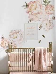 cadre chambre bébé, grandes pivoines roses sur les murs, lit en couleur bronze, cotés du lit bébé recouverts de coussins rectangulaires en tissu rose