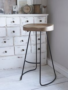 This weathered wooden bar stool has solid seat carved for comfort and elegant aged metal legs.