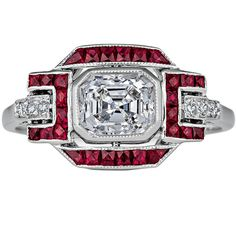 Ruby Diamond Platinum Ring. This spectacular Art Deco inspired ring is the perfect color mix of luscious rubies and sparkling diamonds. With an elegant 1.04 carat antique Asscher cut center diamond surrounded by a total of 1.09 square cut Burmese rubies, the ring sings with the contrast of rich red against fiery white hues. c 2013