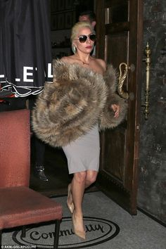She's got style: The Joanne singer looked glamorous in her stylish coat over a slinky grey dress, nude heels and a pair of Ray-Ban sunglasses