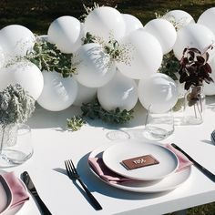 Mother's Day lunch table setting! White balloon floral garland, fresh place settings, with moody touches!