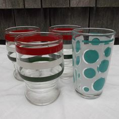 Here is a set of three vintage footed clear glass juice tumblers with red, white and green rings or stripes and one Hazel Atlas turquoise Dots juice