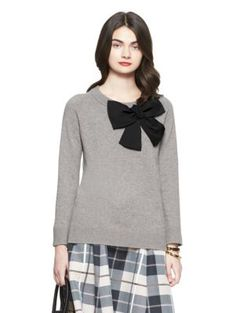 knit from fine merino wool, this crewneck sweater is a great layering piece: not only does it offer warmth, the slightly oversized black bow at the shoulder adds a shot of charm to anything you pair it with.