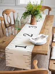 Enlarged tape measure table runner made from fabric drop cloth printed with number and measurements.