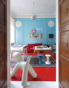 Atmosphère rétro dans ce salon qui laisse toute sa place à la couleur. Utilisée en aplat, la couleur réveille le sol et les plâtres. Le parquet repeint en rouge, et les murs en bleu fifties font de ce salon un temple de la pop culture. Les tabourets tam tam, l'enseigne néon, la boule à facettes et la salle à manger cultivent l'ambiance. Par Côté Maison