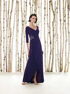 Matte jersey A-line dress with three-quarter length sleeves, V-neckline, side gathered bodice features hand-beaded appliqué, layered mock-wrap skirt with high-low hemline. Sizes:4 – 20, 4P – 14P, 16W – 26W, 16WP – 26WP