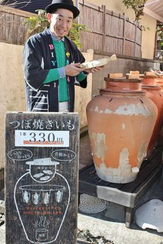 「焼き芋の魅力をデザインの力で発信したい」と話す長橋さん。つぼとお手製の看板が目を引く(神奈川県大磯町で)