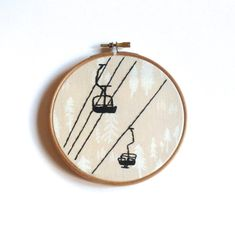 Hand embroidered image of a chairlift silhouette. The design is hand stitched using black DMC threads on Art gallery fabrics Timberland Trunk