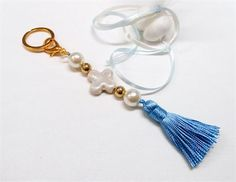 This keychain can also be used as a bag charm and purse charm   These favors are made of:   - porcelain cross in ivory   - silk tassel in blue   - pearls in ivory   - gold plated CCB beads ( a CCB bead is a copper coated acrylic bead)   - gold plated key ring   - big lobster clip   - gold plated findings   - three (3) white Jordan almonds in white tulle tied with satin ribbons in white and blue.   Length: Approx. 16 cm / 6.3 inches   The listing is for ten ( 10) Baptism Favors.