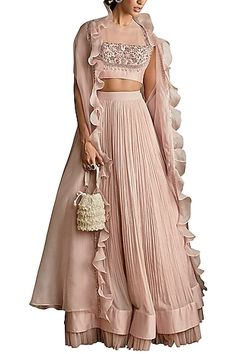 Featuring a pale pink ruched lehenga skirt in pure chiffon, silk chanderi and net base. It is paired with a matching dori blouse in crepe base having hand embroidery and a ruffled cape in organza base.