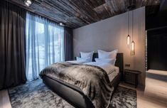 Zhero is a luxury design hotel set amid the Tyrolean Alps in Ischgl. Incorporating Tyrolean tradition and upscale, innovative architecture, the hotel combines smart contemporary design with the comfort of home. The glowing glass façade of the hotel is filtered by rows of vertical wooden planks, reclaimed from local barns and referencing the community's agricultural history. Dark interiors tone with wood ceilings and floors, exposed brick walls, and soft fabrics in dark grey, black, and…