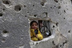 A boy poses for a photograph as he is seen through a hole in a wall in Al-Maliha town, in the suburbs of Damascus, Syria March 16, 2014. REUTERS/Bassam Khabieh