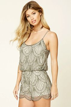 A sleeveless woven romper by Angie™ featuring sheer mesh with sequined and high-polish beaded accents, round neckline, dual straps, a scalloped hem, and a keyhole cutout back.