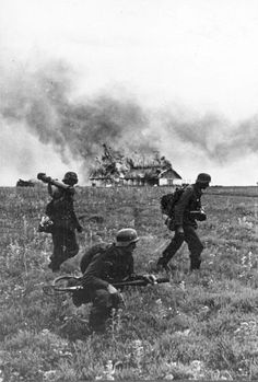 German soldiers of the Großdeutschland Division, one of them equipped with a flamethrower, advance through field during Operation Barbarossa.