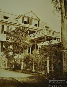 Achtergevel huis met typisch uitgebouwd balkon waarop vaag een manspersoon te zien is. Collectie T. Lens. Datum: 1891-1894 Locatie: Suriname Vervaardiger: Inv. Nr.: SSM-0727-02-54 Fotoarchief Stichting Surinaams Museum