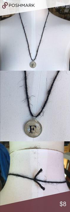 Handmade Black Twine 'F' Initial Necklace Beautiful handmade black twine necklace featuring a silver-coated beige pendant with the initial 'F' in the center. Approx. 12.5 inches long, including pendant. Only one available. Handmade Jewelry Necklaces