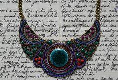 Collier fantaisie de type plastron vert/bleu/violet/rouge, composé de 3 belles pièces articulées en métal doré, rehaussées de petits cabochons, perles, céramique et strass. Au centre, 1 joli palet rond en céramique verte craquelé.