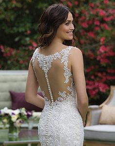 A V-neck fit and flare tulle gown with beaded lace appliqués, illusion back, horsehair hem, and chapel length train that create a classic wedding day look.