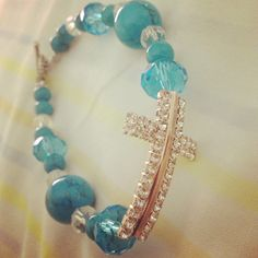 Joyería cruz dorada con piedras azules.