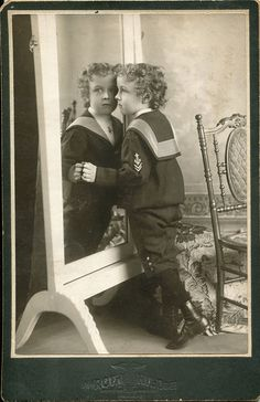 Portrait of a young boy in sailor suit in front of a mirror, by A. M. Rothschild & Co.