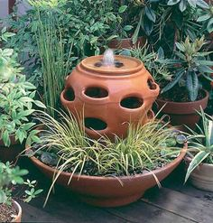 Planter Fountain.  In this simple homemade fountain, an azalea container supports a strawberry pot and hides a small water pump; a low terra-cotta bowl forms the base and catches falling water.