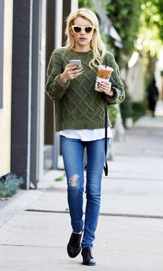 Emma Roberts wears a cable knit green sweater, t-shirt, jeans, oxfords, and cat-eye sunglasses
