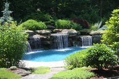 This backyard landscaping and water feature swimming pool is in Woodcliff Lake, Bergen County , NJ. The man made waterfalls are constructed of Pa. colonial blue stone boulders.  Large slab bluestone garden pathway stones lead to the pool. The patio is a grey Tennessee crab orchard stone.  Behind the water is a large Picea abies Nidiformis with two Acer palmatum dissectum Red Select.  For late summer there are Nipponanthemum nipponicum flowering white with yellow centers.