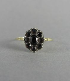 This beautiful paste ring was hand converted from a Georgian era pin. It features a cluster of mine cut paste glass gems set in silver over gold. The paste gems have a very interesting color, they look dark blue or black indoors and orangey green in direct sunlight. A very interesting and unusual color change.  The shank of this ring is handmade from 14k gold and features some decorative filing at either side of the paste center, it is inspired by the shank of a Georgian era ring in my…