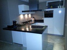 Greeploze wit glanzende U-keuken met schiereiland en zitgedeelte — in Helmond.