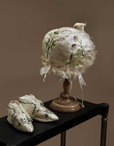 Pair of infant's shoes and a cap, France or England, 1760-1800. Ivory silk satin with polychrome floral silk embroidery.