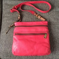 Fossil coral/reddish Crossbody bag Beautiful Fossil Leather coral/reddish Crossbody bag. Adjustable strap, 2 large exterior pockets. Gold tone hardware. Inside has 1 zippered pocket and 2 media pockets. Bag has a few minor scratches, hardly noticeable. NWOT. I received this bag as a gift and never used it. Hoping to find it a new home.  Fossil Bags Crossbody Bags