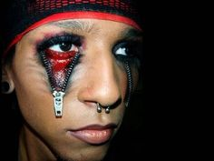 Apply the zipper eye makeup Halloween costume look by gluing real zippers below your eye. This gives a really creepy, skin opening look. Make it more gruesome with fake blood and darker eye makeup. It's originally a MAC makeup look, but many use it for scary costuming or an industrial zombie look.