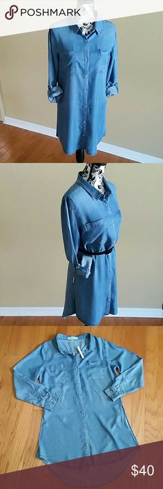 """CHAMBRAY BUTTON FRONT TUNIC TOP SIDE SLITS Thread Supply Chambray button front tunic top with long sleeves and collar. Sleeves can be rolled up and have tabs to create 3/4 length sleeves. Very soft and flowy. Has high low rounded hem. Longer length with side slits. Style with or without belt, open or buttoned. Lots of options! 100% lycosel Armpit to armpit 21"""" across laying flat  Shoulder to hem 34.5"""" front 38"""" back.  Size Medium  New with tag  (price tag removed but still has a hanging tag…"""