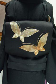 黒の地に、金駒刺繍であしらわれた金と銀の蝶々が浮かぶ名古屋帯です。