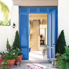 Apply the character of the coast to your home's exterior with beach house-style architecture and accents of vibrant color. A Caribbean blue louvered doorway adds flair and beckons guests inside.