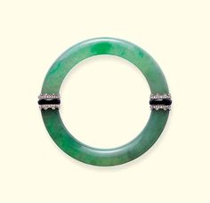A BELLE EPOQUE JADEITE, DIAMOND AND ONYX BANGLE  In the style of a hololith, the jadeite bangle to the diamond and onyx concealed clasp and hinge of similar design, circa 1912, 17.1 cm. inner circumference, in red leather Cartier case.