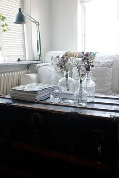 a wooden trunk turn a coffee table, or could be a pile of vintage luggage, + glass vases + french industrial lamp = joy