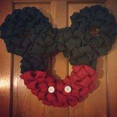 """Brings Disney into your home with this fun Mickey inspired wreath. This is a rather large wreath with a 14"""" center and those iconic ears are 8"""" each. Mickey's look is completed with two white buttons.  $55.00 is all you need to pick it up from ArcherAlley Esty shop but only ONE is remaining so don't miss the opportunity to surprise your kids with a Mickey Wreath for the start of the summer vacation."""