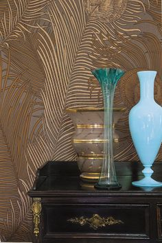 A bronze with metallic detailing wallpaper pattern featuring an elegant motif of a large scale peacock feather.