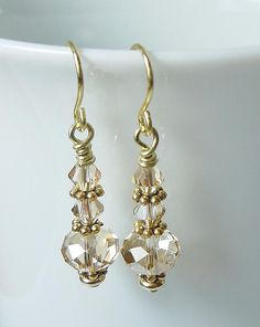 The pretty earrings are made with beautiful Swarovski Crystal Golden Shadow beads that shimmer like only Swarovski can! They are made with gold-filled components and ear wires and hang approximately 1 in length. We can make them in several other colors. Please convo us for the