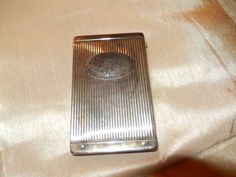 A metal case to carry credit cards or hand made thin cigarettes. Measures 3 7/8 h x 2 3/8 w. Has a push button mechanism to open it.